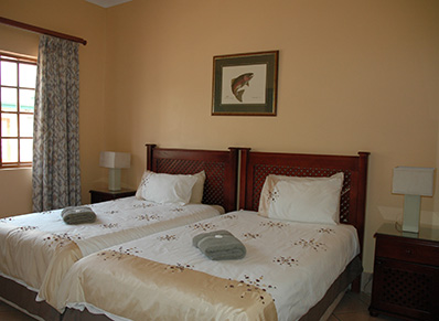 bedroom with two 3/4 beds, en suite bathroom comprising shower, washbasin in marble top and toilet.