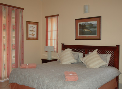 Bedroom with king size bed, en suite bathroom comprising oval bath, deluxe shower, washbasin in marble top, and toilet.