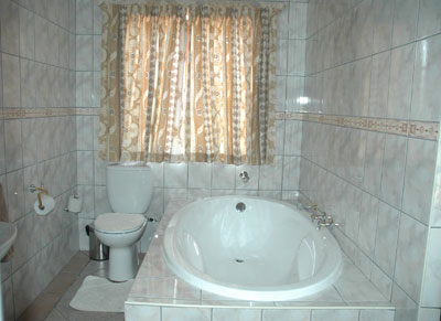 Bathroom with an oval bath, washbasin in marble top and a toilet.
